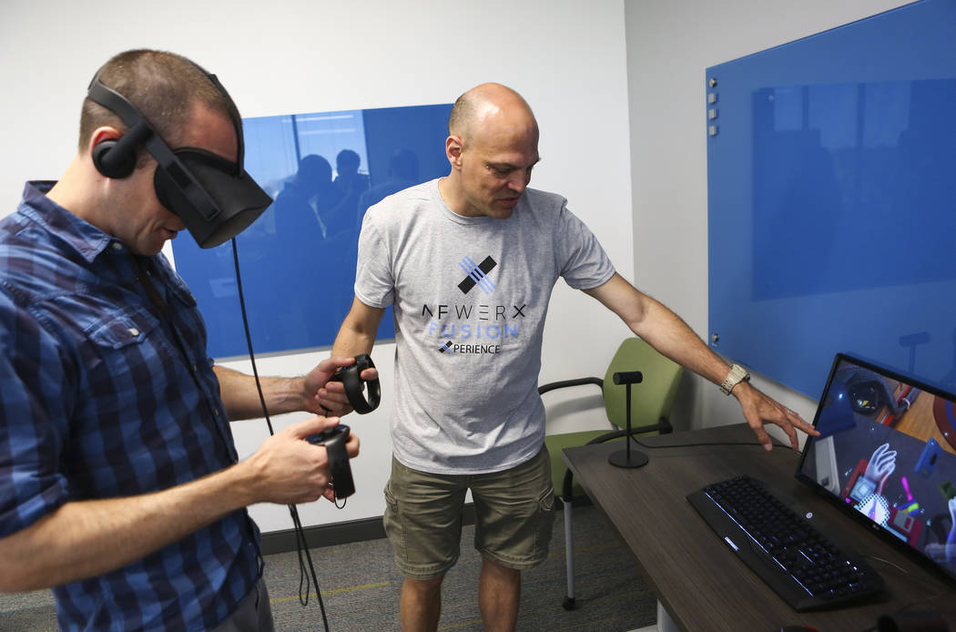 Barron Stone, left, picks up items using a virtual reality headset with the help of MSgt. Powell Crider at the grand debut of the completed Innovation Center and Prototyping Lab at AFWERX Vegas in ...