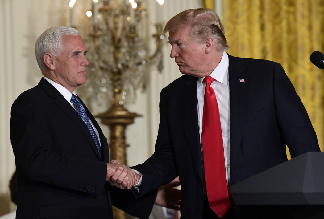 President Donald Trump shakes hands with Vice President Mike Pence during a meeting of the National Space Council in the East Room of the White House, Monday, June 18, 2018, in Washington. (AP Pho ...