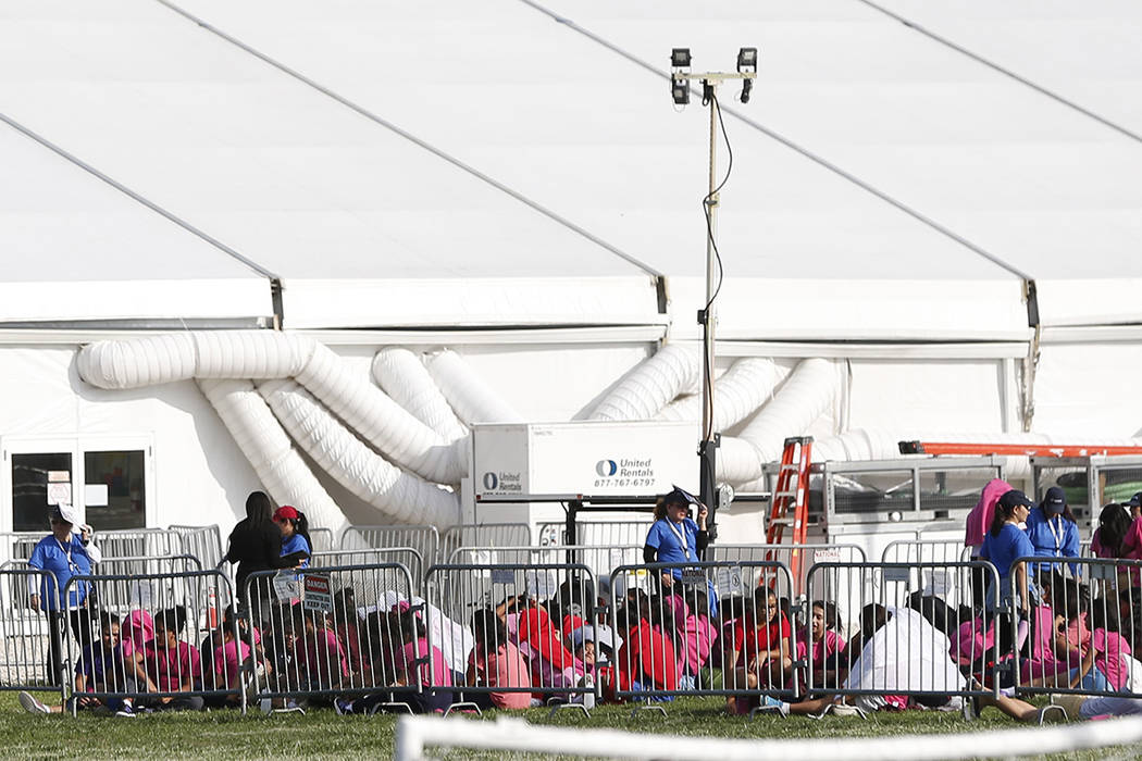Immigrant children are shown outside a former Job Corps site that now houses them, Monday, June 18, 2018, in Homestead, Fla. It is not known if the children crossed the border as unaccompanied min ...