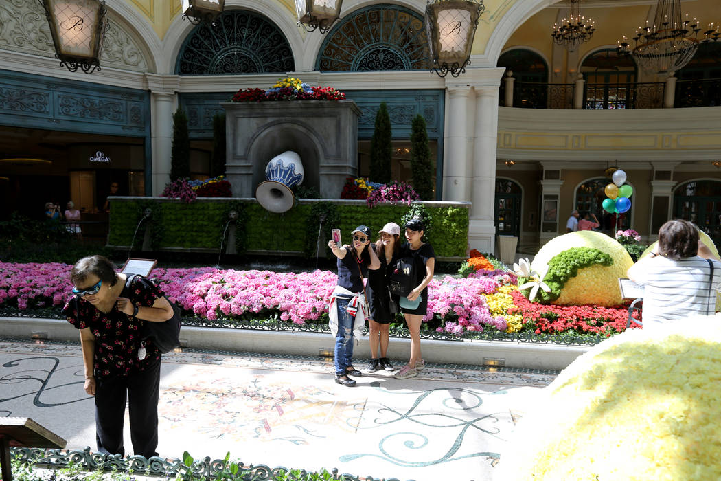 Friends from Thailand, from left, Lek Mongkolwajanarat, Nok Khonthai and Tan Ampornchai Sakul poses at ÒThatÕs AmorŽ,Ó the Bellagio Conservatory's summer display Monday, June ...