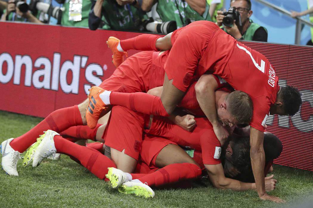 England's Harry Kane is cheered by teammates after scoring during the group G match between Tunisia and England at the 2018 soccer World Cup in the Volgograd Arena in Volgograd, Russia, Monday, Ju ...
