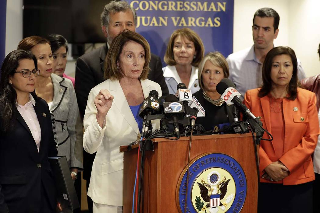 House Minority Leader Nancy Pelosi, D-Calif., at podium, speaks in front of members of the Congressional Hispanic Caucus during a visit to the border Monday, June 18, 2018, in San Diego. The membe ...