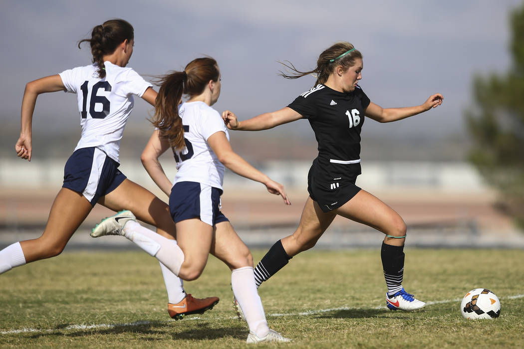 Palo Verde's Olivia Packer, right, moves the ball past Centennial's Savannah Tarone, left, and Brooke Hawley (15) during a soccer game at Centennial High School in Las Vegas on Tuesday, Sept. 19, ...