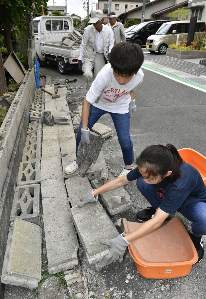 Residents clean up debris in Ibaraki, Osaka, western Japan, Tuesday, June 19, 2018. The magnitude 6.1 earthquake that struck the area early Monday damaged buildings and left many homes without w ...