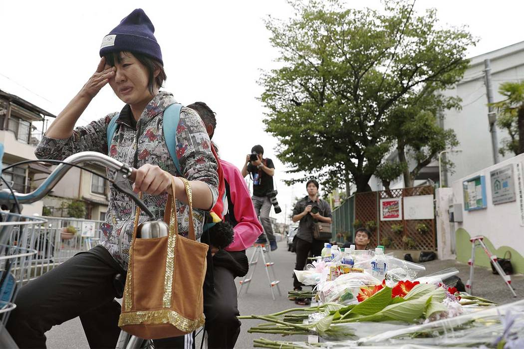 A woman reacts near flowers near the site where a concrete wall at an elementary school fell onto the street and killed a 9-year-old, in Takatsuki, Osaka, western Japan, Tuesday, June 19, 2018. R ...