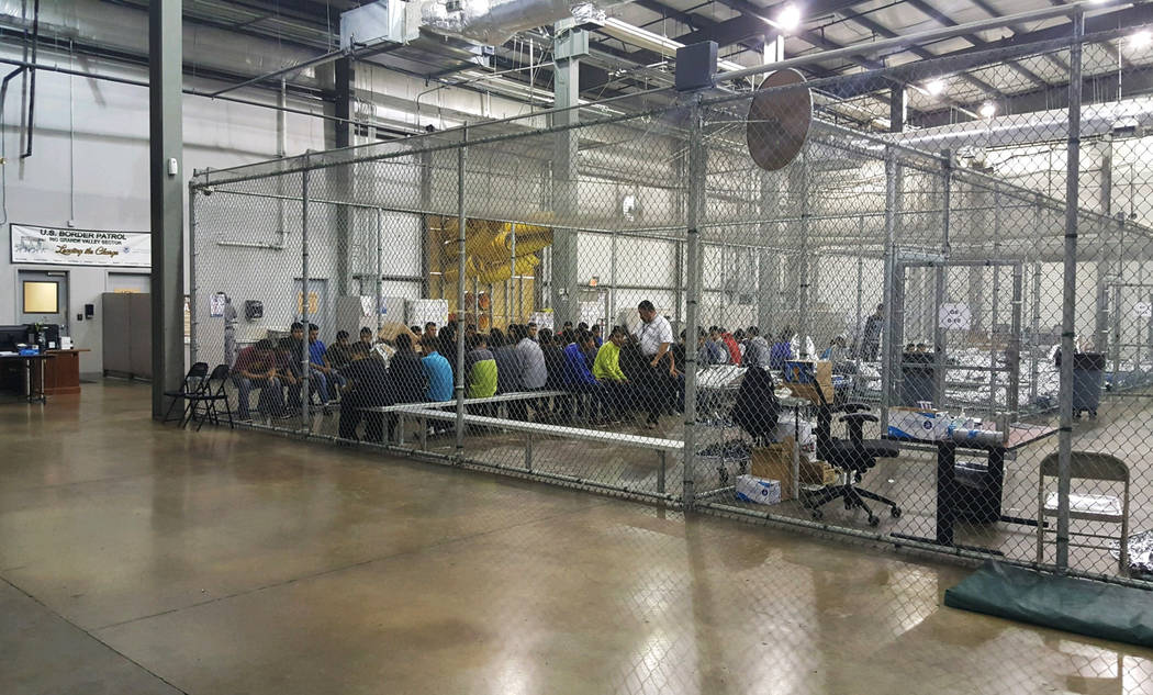In this photo provided by U.S. Customs and Border Protection, people who've been taken into custody related to cases of illegal entry into the United States, sit in one of the cages at a facility ...