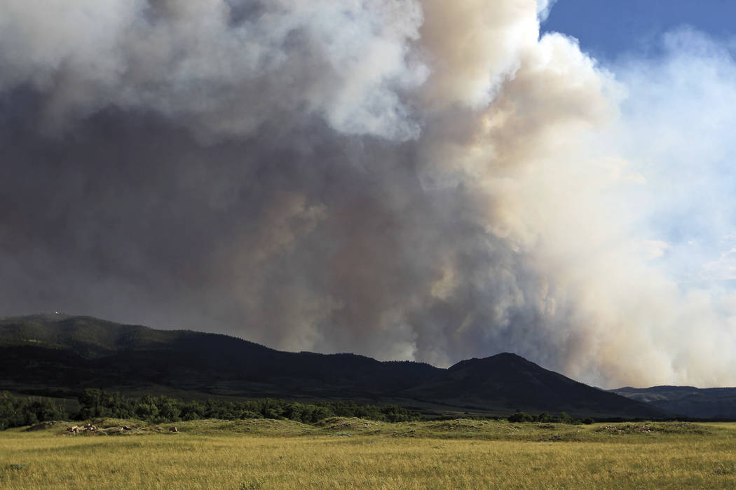 Smoke from a wildfire drifts past Jelm Mountain, as seen from Highway 230 near Woods Landing, Wyomng. (Shannon Broderick/Laramie Boomerang via AP)