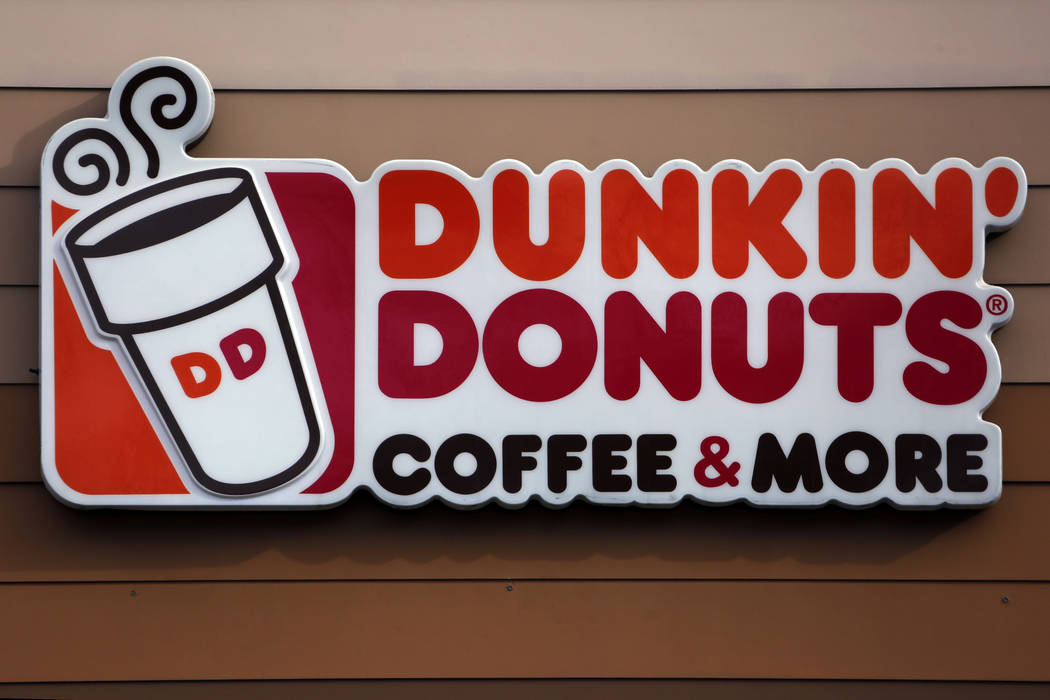 FILE- This Jan. 22, 2018, file photo shows the Dunkin' Donuts logo on a shop in Mount Lebanon, Pa. A Dunkin' Donuts shop in Baltimore is no longer offering customers coupons if they report workers ...