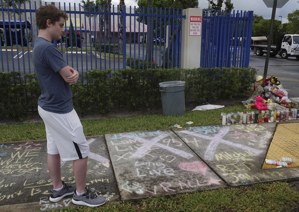 A fan of rap singer XXXTentacion pauses by a memorial, Tuesday, June 19, 2018, outside Riva Motorsports in Deerfield Beach, Fla., where the troubled rapper-singer was killed the day before. (Joe C ...