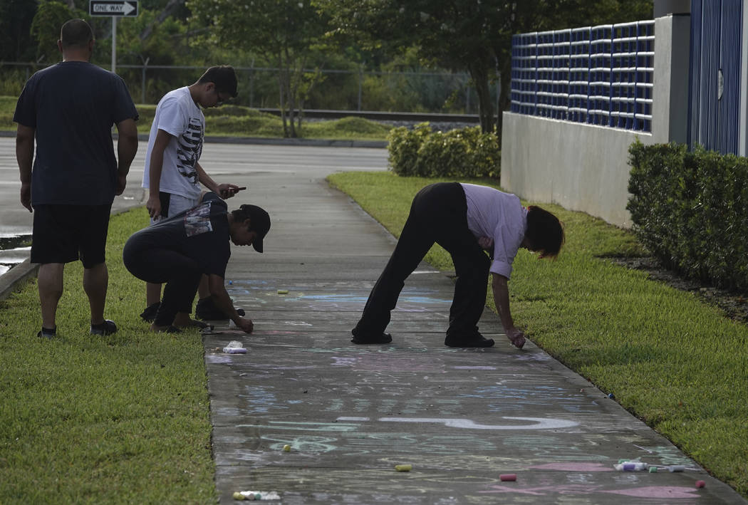 Fans and mourners of rap singer XXXTentacion write a messages on the sidewalk, Tuesday, June 19, 2018, outside Riva Motorsports in Deerfield Beach, Fla., where the troubled rapper-singer was kille ...