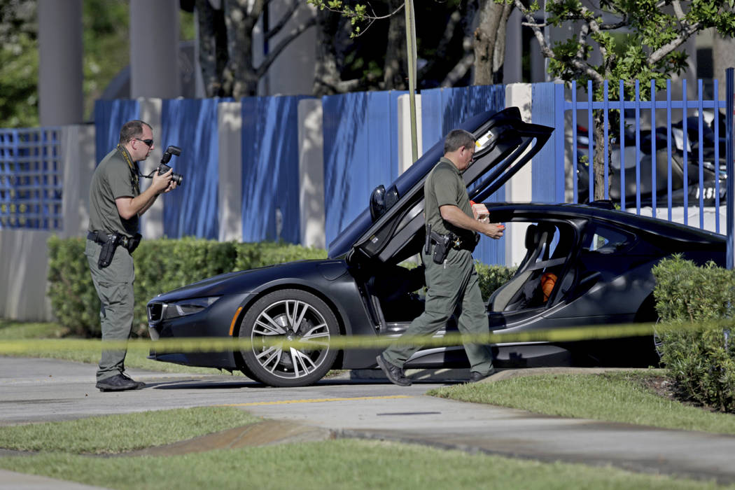 Investigators surround a vehicle after rapper XXXTentacion was shot on Monday, June 18, 2018, in Deerfield Beach, Fla. The Broward Sheriff's Office says the 20-year-old rising star was pronounced ...