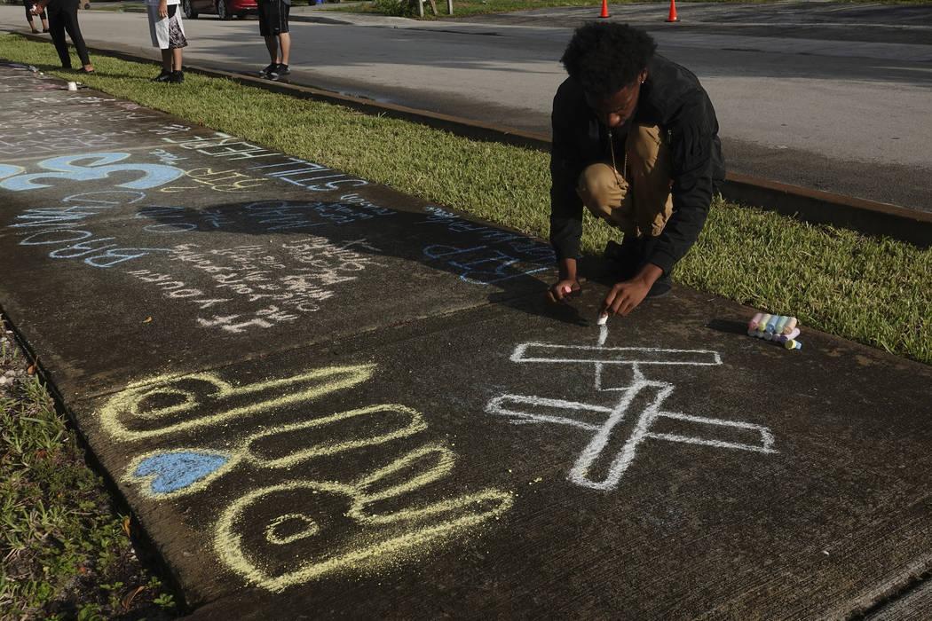 Lenar Nesmith, of Pompano Beach, Fla., a fan of rap singer XXXTentacion, writes a message on the sidewalk, Tuesday, June 19, 2018, outside Riva Motorsports in Deerfield Beach, Fla., where the trou ...