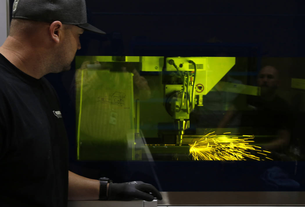Jordan Yost, co-owner of Precision Tube Laser, LLC, watches as the TruLaser Tube 5000 laser cutting machine cuts out a piece of metal on Wednesday, June 20, 2018, in Las Vegas. Bizuayehu Tesfaye/L ...