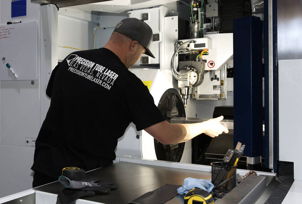 Jordan Yost, co-owner of Precision Tube Laser, LLC, places a metal pipe into the TruLaser Tube 5000 laser cutting machine on Wednesday, June 20, 2018, in Las Vegas. Bizuayehu Tesfaye/Las Vegas Rev ...