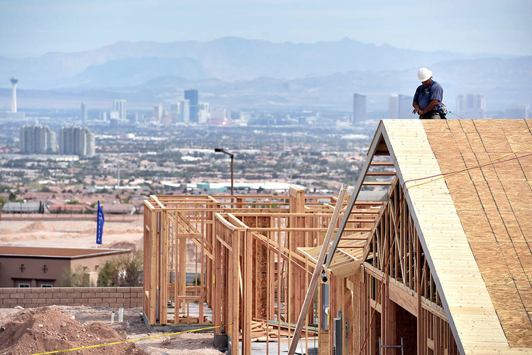 A carpenter works on the roof of a new home under construction at the western edge of Las Vegas in 2015. (Las Vegas Review-Journal)