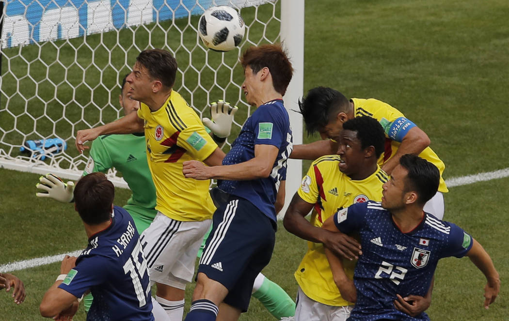 Japan's Yuya Osako, center, scores his side second goal during the group H match between Colombia and Japan at the 2018 soccer World Cup in the Mordavia Arena in Saransk, Russia, Tuesday, June 19, ...