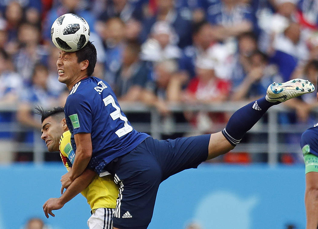 Japan's Gen Shoji gets above Colombia's Radamel Falcao to win a header during the group H match between Colombia and Japan at the 2018 soccer World Cup in the Mordavia Arena in Saransk, Russia, Tu ...