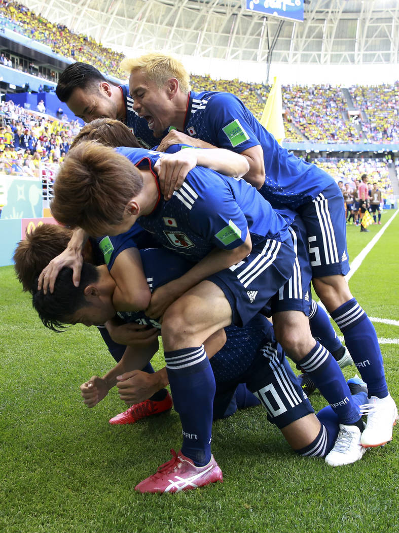 Teammates crowd over Japan's Shinji Kagawa after he scored from the penalty spot his side's first goal against Colombia during a group H match at the 2018 soccer World Cup in the Mordavia Arena in ...