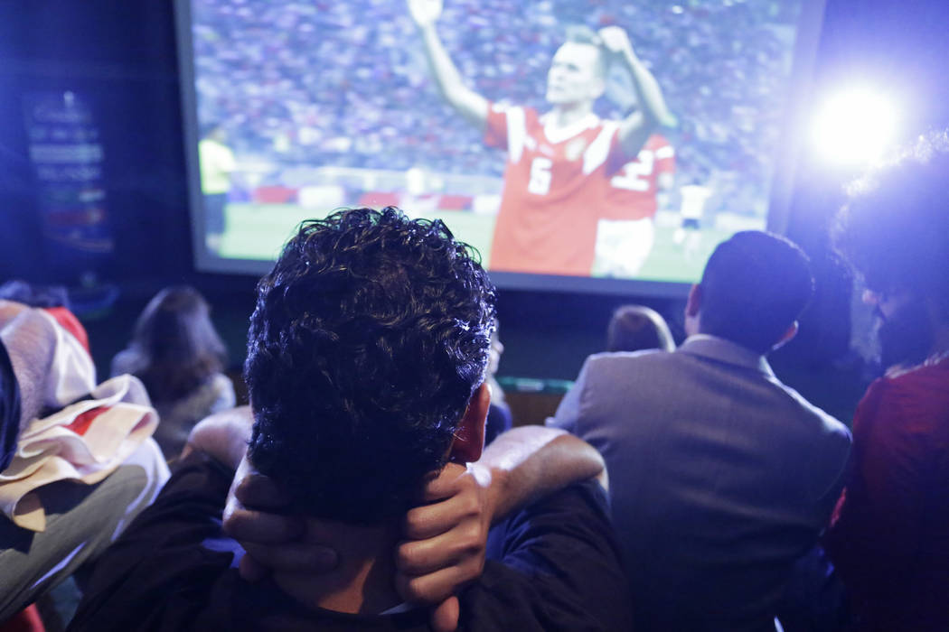 A Egypt soccer fan reacts as he watches Russia score during the World Cup match between Russia and Egypt, in Sao Paulo, Brazil, Tuesday, June 19, 2018. Russia won the match 3-1. (AP Photo/Nelson A ...