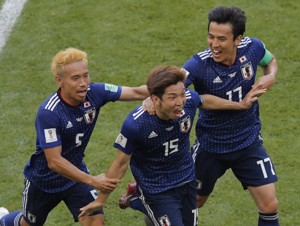 Japan's Yuya Osako, centre, celebrates after scoring his side's 2nd goal with teammates Makoto Hasebe, right, and Yuto Nagatomo, left, during the group H match between Colombia and Japan at the 20 ...