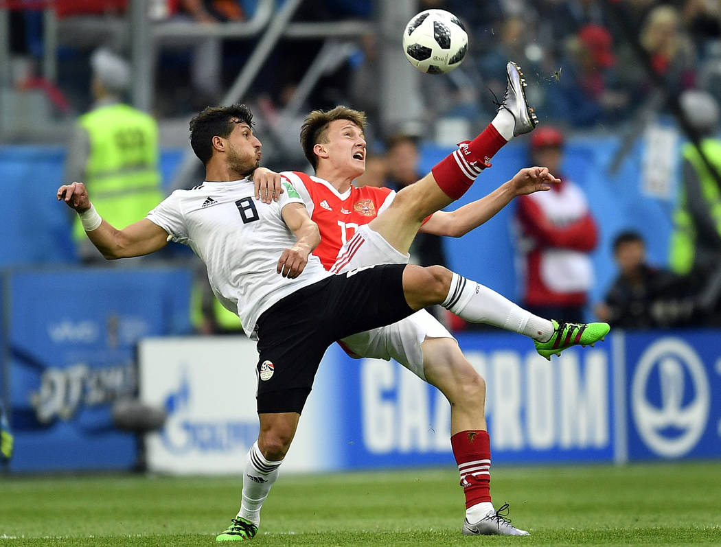 Egypt's Tarek Hamed, left, and Russia's Alexander Golovin compete for the ball during the group A match between Russia and Egypt at the 2018 soccer World Cup in the St. Petersburg stadium in St. P ...