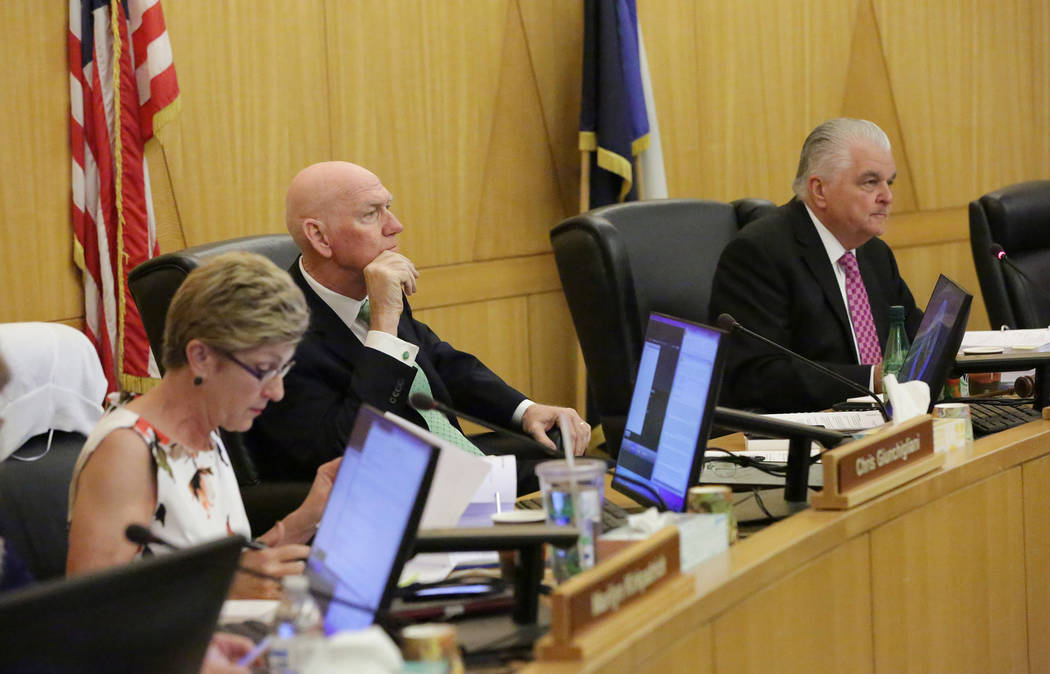 Clark County Commissioners Chris Giunchigl?iani, left, Larry Brown and Steve Sisolak listen to comments from the public before voting on a resolution seeking federal legislation to open almost 39, ...