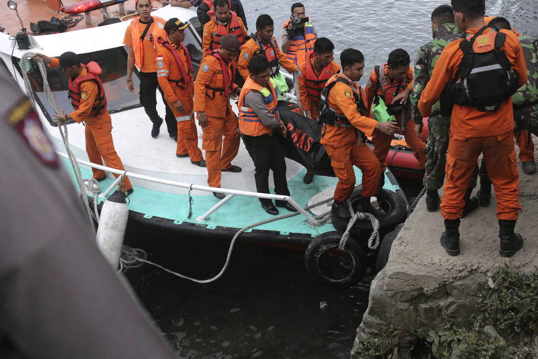 Indonesian search and rescue team carry a victim body of a ferry sinking at Tigaras port in Toba lake, North Sumatra, Wednesday, June, 20, 2018. The boat, overcrowded with passengers and motorbike ...