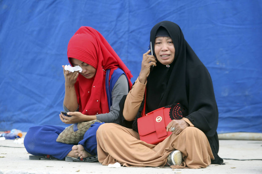 Relatives weep at Tigaras port after learning that their family members are among the passengers of a ferry which sank on Monday, in Lake Toba, North Sumatra, Indonesia Wednesday, June, 20, 2018. ...