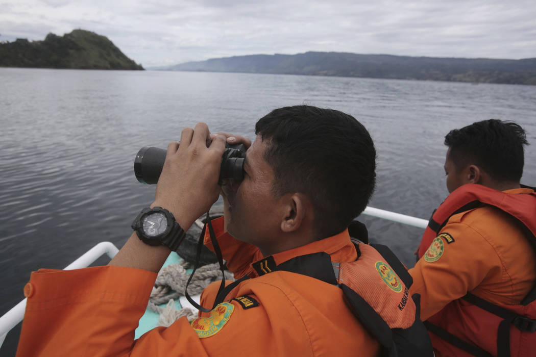 Indonesian rescuers scan the horizon from the deck of a rescue ship as they search for a ferry which sank on Monday in Lake Toba, North Sumatra, Indonesia, Wednesday, June, 20, 2018. Distraught re ...
