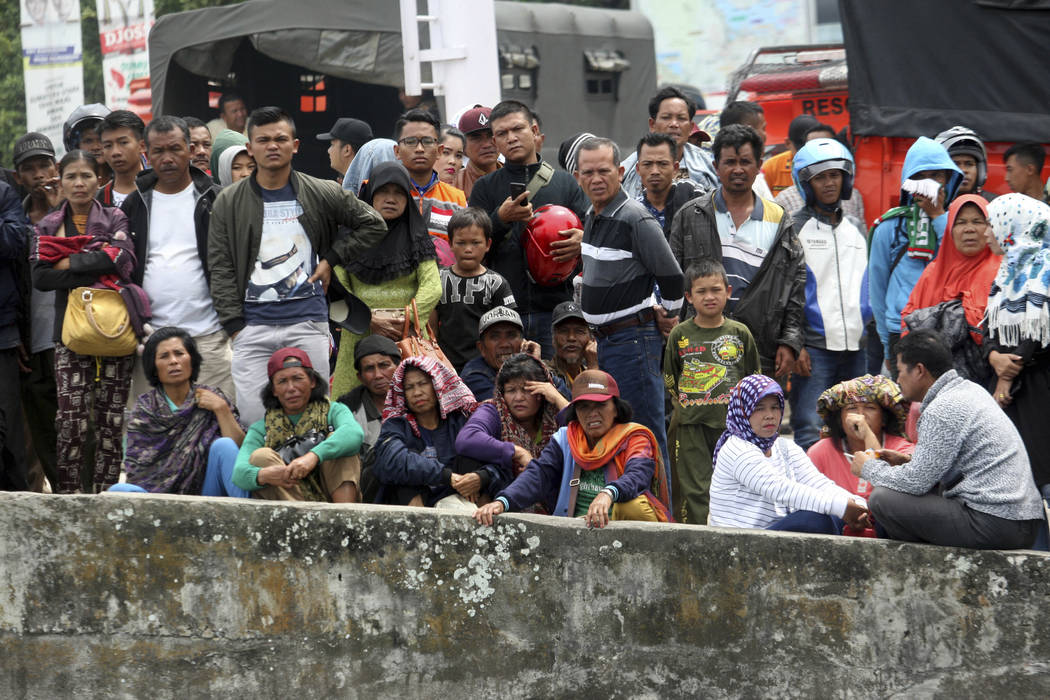Relatives of a ferry sank wait at Tigaras port in Toba lake, North Sumatra, Wednesday, June, 20, 2018. Distraught relatives slammed Indonesia's government for not enforcing basic safety measures o ...