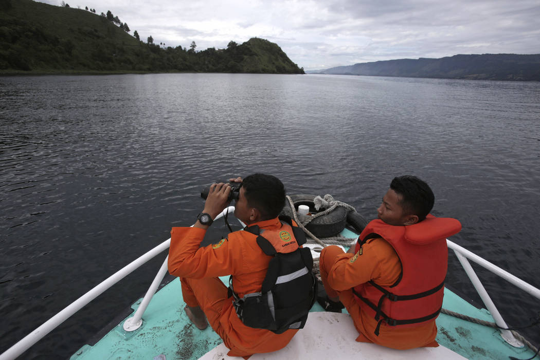 Indonesian search and rescue team scan the horizon from the deck of a rescue ship during their search for a ferry which sank Monday in Lake Toba, North Sumatra, Wednesday, June, 20, 2018. Distraug ...