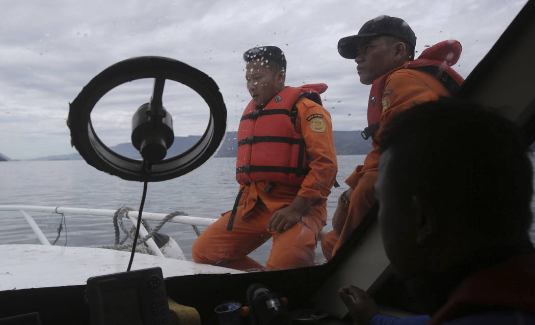 Emergency rescue team members search for victims from a sunken ferry on Toba lake, North Sumatra, Indonesia, Wednesday, June, 20, 2018. Officials said that over a hundred people are still missing ...