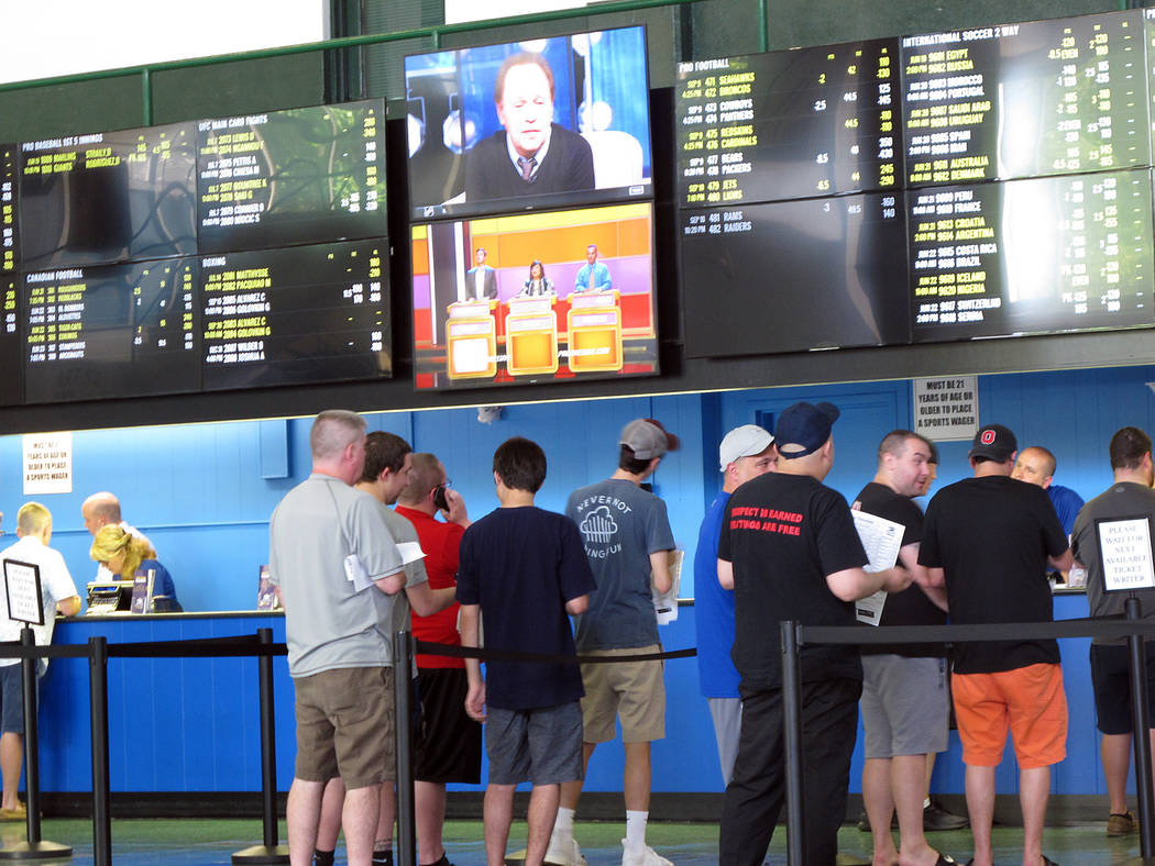 Bettors line up at windows at Monmouth Park racetrack in Oceanport, N.J., to make sports bets. Monmouth Park and Atlantic City's Borgata casino say they're pleased with the extra revenue sports be ...
