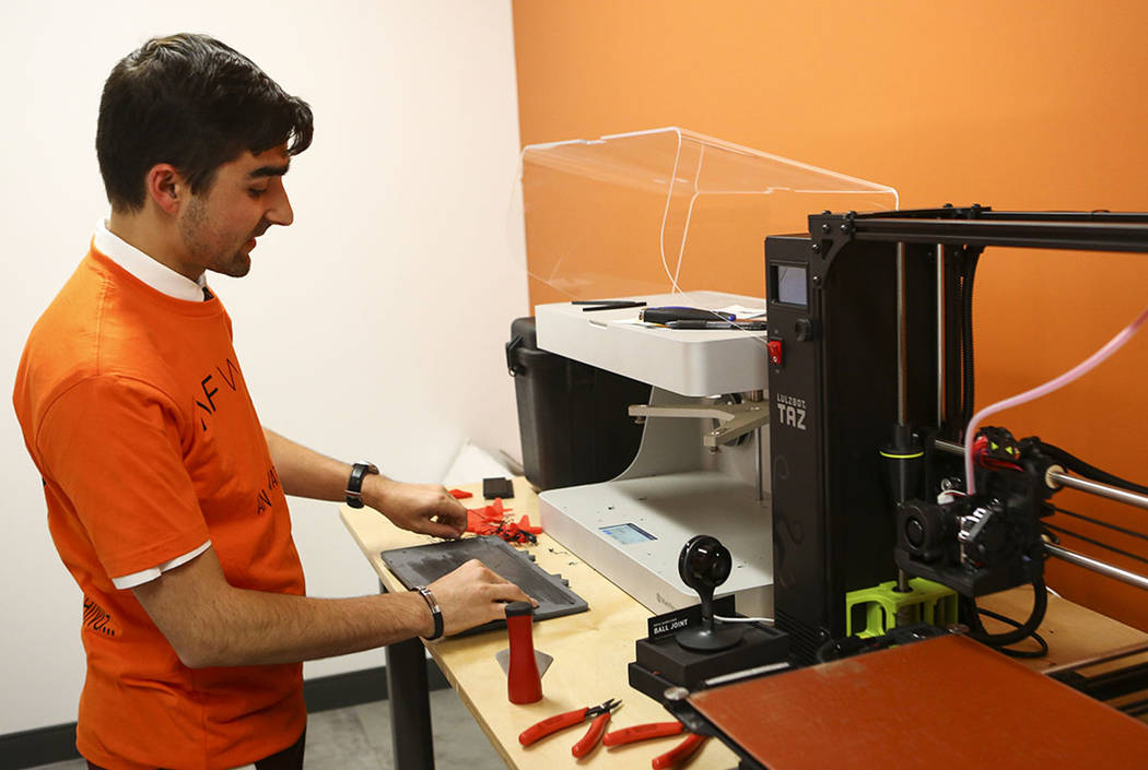 Matthew Viton, prototyping lab coordinator, looks at a 3D printer during a tour of the lab at the grand debut of the completed Innovation Center and lab at AFWERX Vegas in Las Vegas on Tuesday, Ju ...