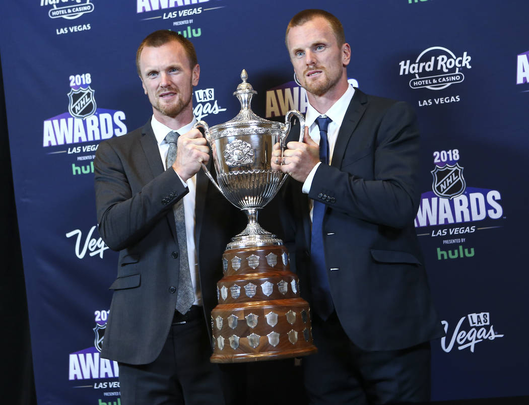 Henrik Sedin, left, and Daniel Sedin of the Vancouver Canucks pose with the King Clancy Memorial Trophy during the NHL Awards at the Hard Rock Hotel in Las Vegas on Wednesday, June 20, 2018. Chase ...