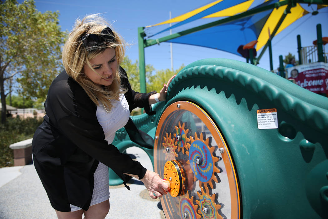 Councilwoman Michele Fiore shows the newly installed sensory wall at Gilcrease Brothers Park in Las Vegas, Saturday, June 23, 2018. The sensory wall is the first to be installed in a city park acc ...