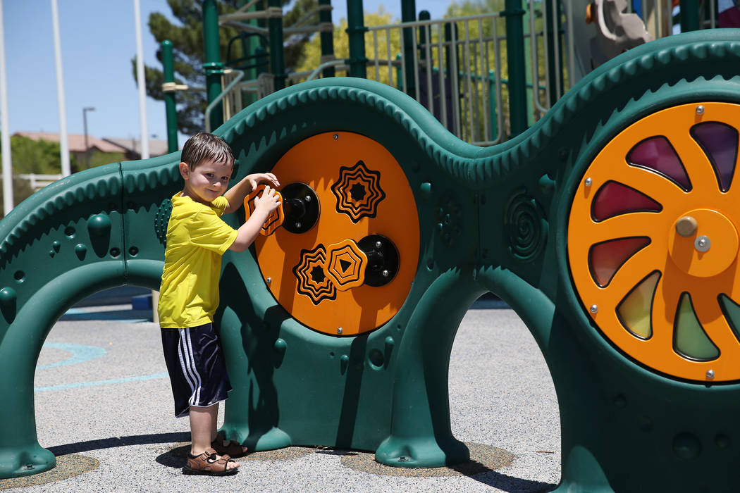 Gunnar Anderson, 4, plays with the newly installed sensory wall at Gilcrease Brothers Park in Las Vegas, Saturday, June 23, 2018. The sensory wall is the first to be installed in a city park accor ...