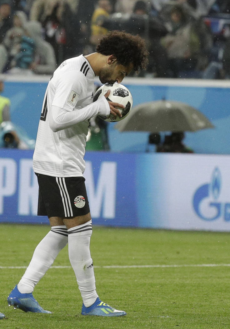 Egypt's Mohamed Salah kisses the ball before scoring his sides first goal from a penalty kick during the group A match between Russia and Egypt at the 2018 soccer World Cup in the St. Petersburg s ...