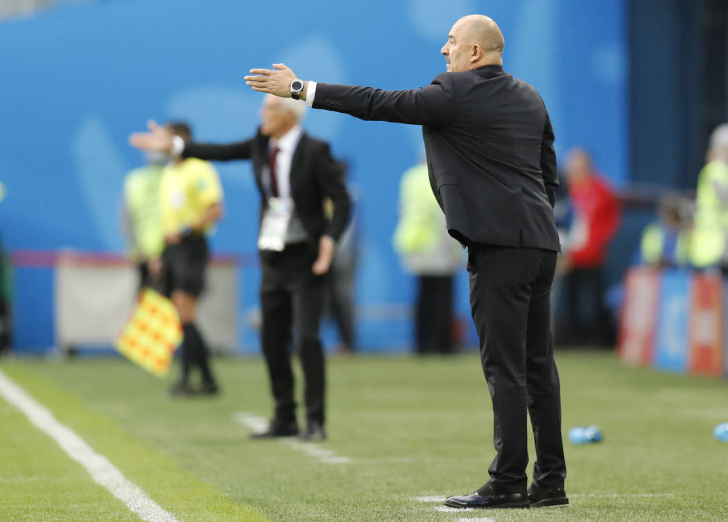 Russia head coach Stanislav Cherchesov, right, and Egypt head coach Hector Cuper, center, gesture during the group A match between Russia and Egypt at the 2018 soccer World Cup in the St. Petersbu ...