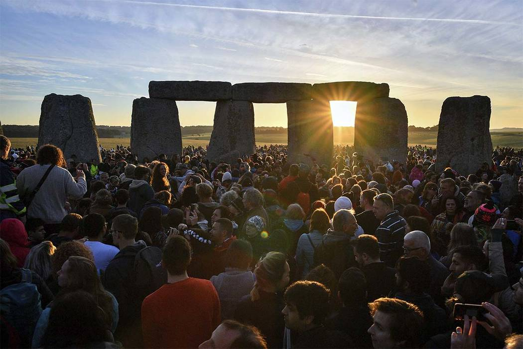 The sun rises through the stones at Stonehenge as crowds of people gather to celebrate the dawn of the longest day in the UK, in Wiltshire, England, Thursday June 21, 2018. (Ben Birchall/PA via AP)