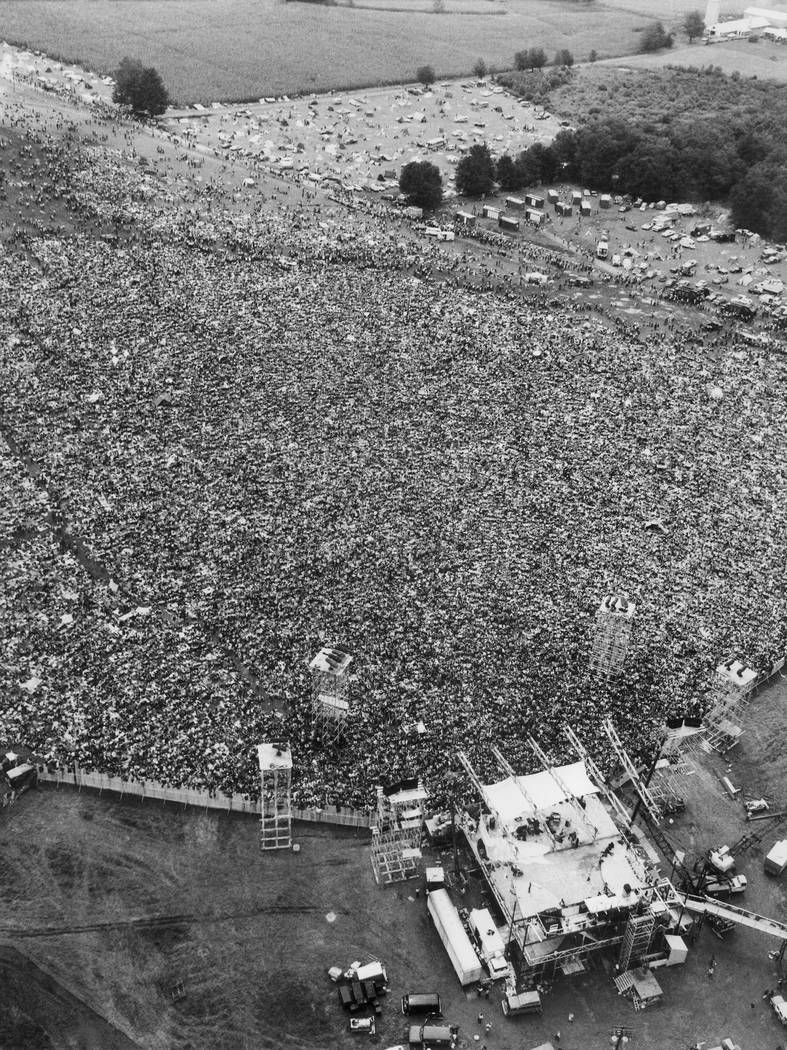 FILE - In this August 16, 1969 file aerial photo, music fans at the original Woodstock Music and Arts Festival are packed around the stage, at bottom, in Bethel, N.Y. Archaeologists from New York' ...