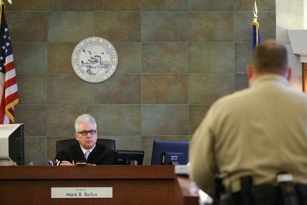 District Judge Mark Bailus, left, listens to Las Vegas police officer Jeremy Robertson, during the sentencing hearing for Clemon Hudson and Steven Turner, who were convicted of attempted murder fo ...
