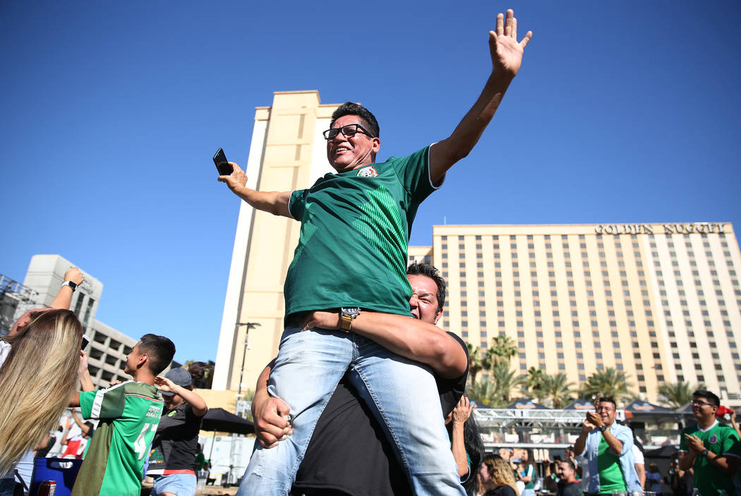 Danny Rubi Geraldo lifts his uncle Esteban Geraldo in celebration of a goal by Mexico against South Korea during a watch party of the World Cup soccer match at the Downtown Las Vegas Events Center ...