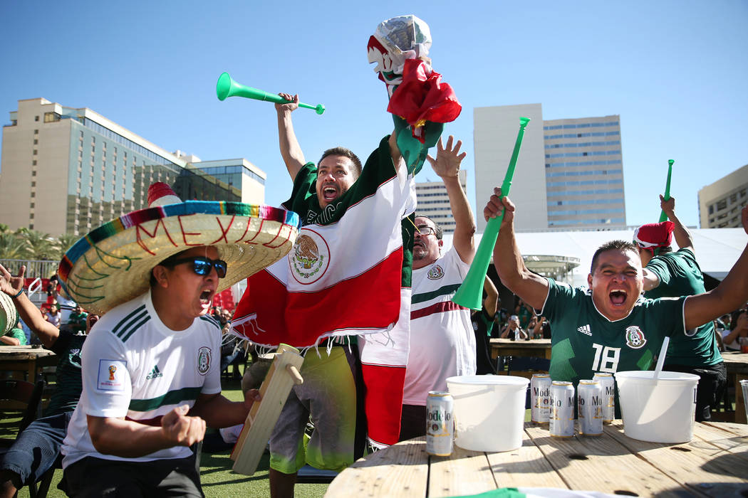Milo Nino, from left, Juan Jimenez, Luis Vides, and Juan Paredes, celebrate a goal by Mexico against South Korea during a watch party of the World Cup soccer match at the Downtown Las Vegas Events ...