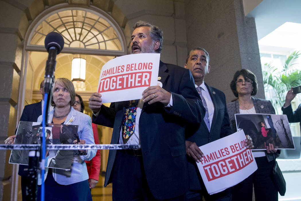 "From left, Hispanic Caucus Chair Rep. Michelle Lujan Grisham, D-N.M., Rep. Juan C. Vargas, D-Calif., Rep. Adriano Espaillat, D-NY, and Rep. Linda Sanchez, D-Calif., hold signs that reads ""Fam ..."