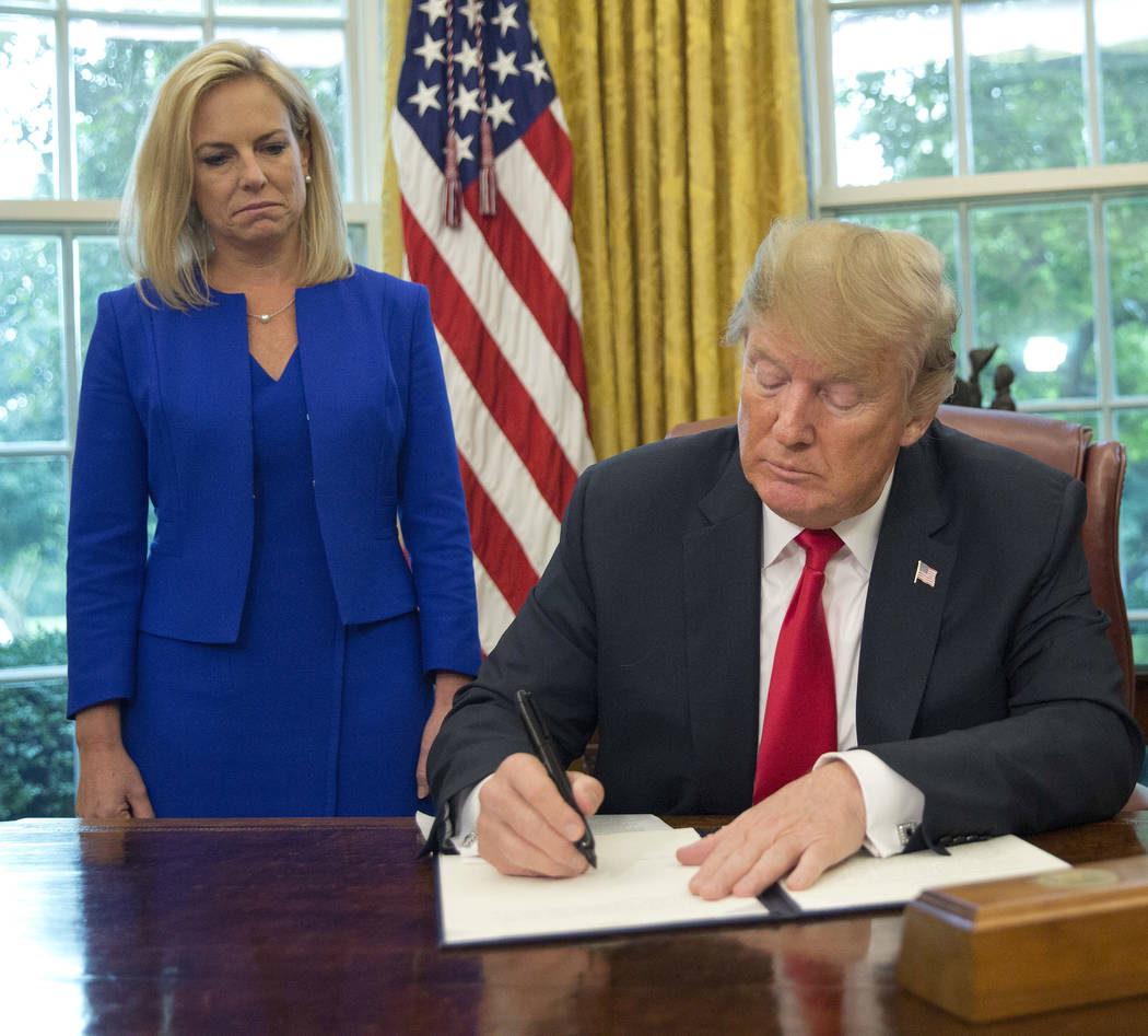 President Donald Trump signs an executive order to end family separations, during an event in the Oval Office of the White House in Washington, Wednesday, June 20, 2018. Standing behind Trump are ...
