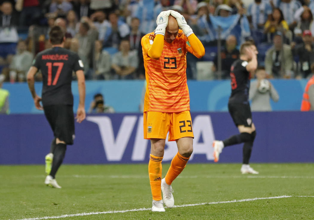 Argentina goalkeeper Wilfredo Caballero holds his head after Croatia's Ante Rebic, background right, scored the opening goal during the group D match between Argentina and Croatia at the 2018 socc ...