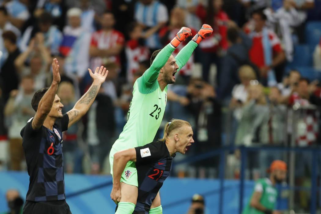 Croatia's Dejan Lovren, left, goalkeeper Danijel Subasic, top, and Domagoj Vida celebrate at the end of the group D match between Argentina and Croatia at the 2018 soccer World Cup in Nizhny Novgo ...
