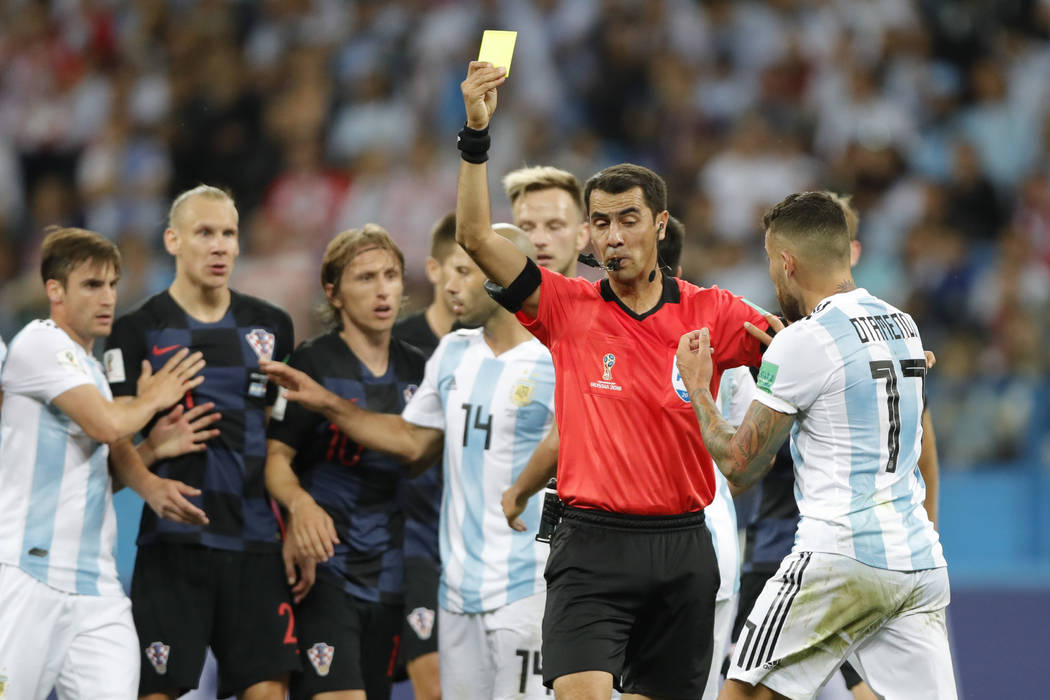 Argentina's Nicolas Otamendi, right, is shown a yellow card by Uzbekistan's referee Ravshan Irmatov during the group D match between Argentina and Croatia at the 2018 soccer World Cup in Nizhny No ...