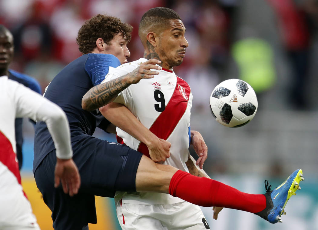 Peru's Pablo Guerrero, right, is challenged by France's Benjamin Pavard during the group C match between France and Peru at the 2018 soccer World Cup in the Yekaterinburg Arena in Yekaterinburg, R ...